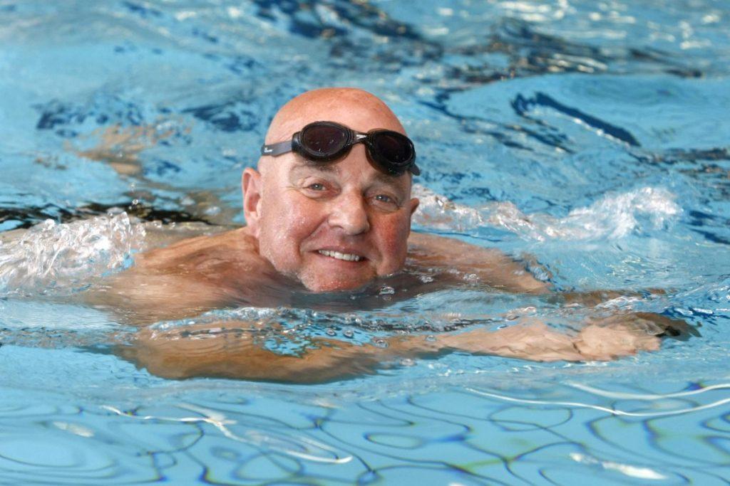 Afbeelding oudere heer in zwembad met schoolslag