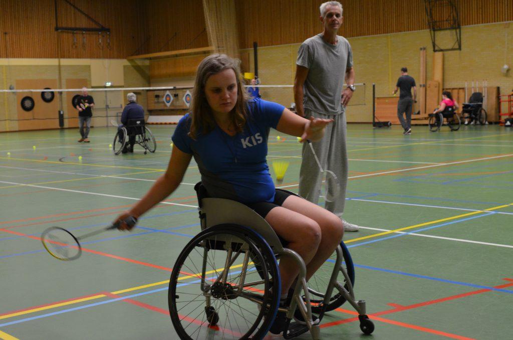 Afbeelding van een jeugdspeler welke vanuit een sportrolstoel aangepast badminton speelt