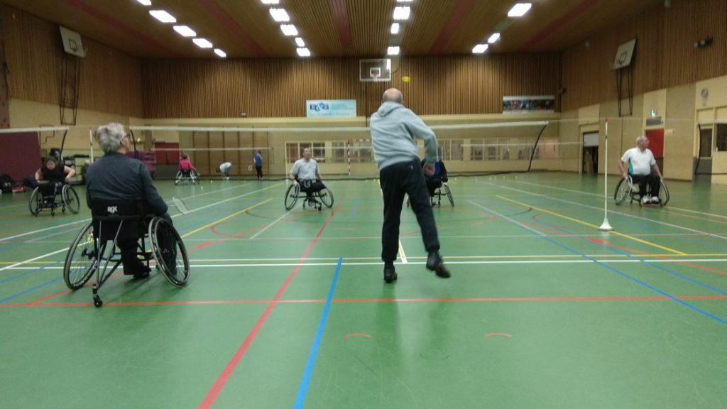 afbeelding van spelers vanuit sportrolstoel en spelers die minder mobiel zijn die samen aangepast badminton spelen.